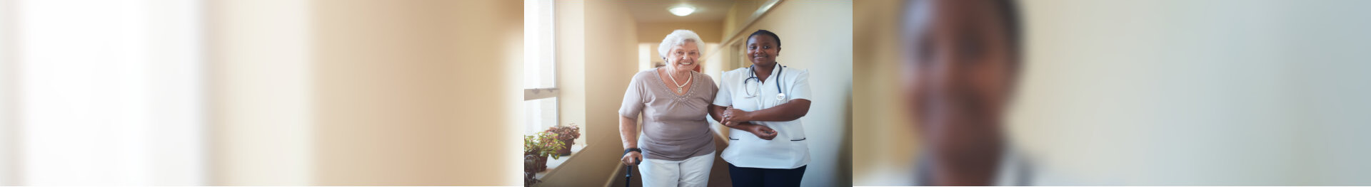 caring female caregiver assisting elderly woman to walk.